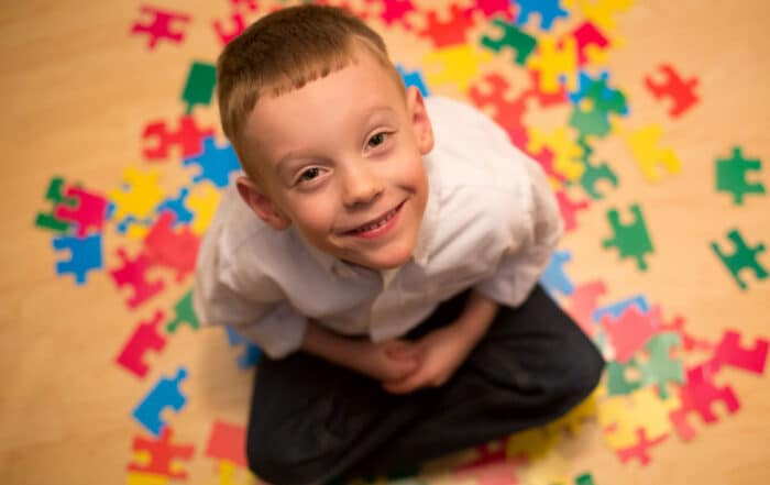 child with autism sitting down and looking up smiling